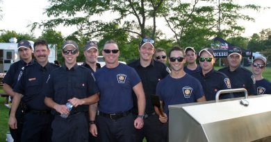 Ottawa Fire Station 64 volunteer firefighters take a break from the barbecue to pose for a photo. Photo by Jake Davies