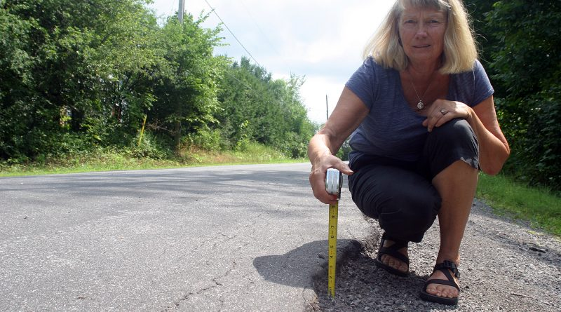 rest Road resident Judy Henry shows off the nearly three-inch curb causing havoc on pedestrians and cyclists on Stonecrest Road. Photo by Jake Davies