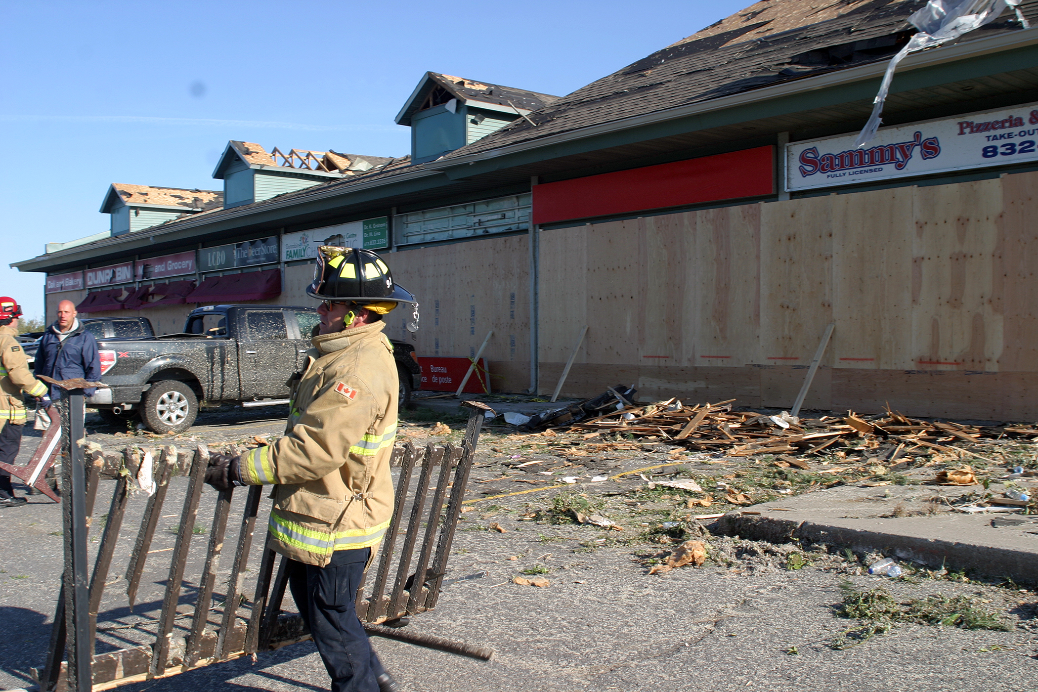 Firefighters, business owners and volunteers clear debris from the mini-mall in Dunrobin. Photo by Jake Davies