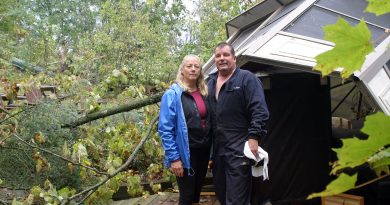 Heather and Allan Gallagher pose by their toppled gazebo. They have spent the last five days cleaning up from last Friday's tornado. Photo by Jake Davies