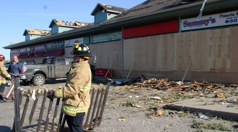 Firefighters clear debris at the Dunrobin mall. Ten days after the tornado destroyed their business, Dunrobin Family Chiropractic has re-opened in a new location. Photo by Jake Davies