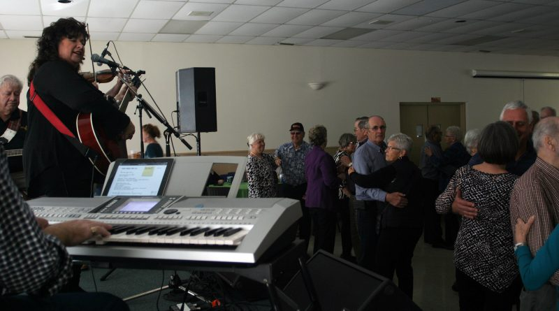 Hall of Famer Lauren Hall entertains a full dance floor at Sunday's Neighbours Helping Neighbours event in Kinburn. Photo by Jake Davies