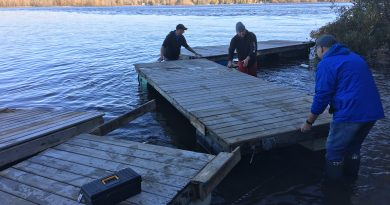 Modern Niagara employees brave the frigid Ottawa River to help bring in docks for the winter. Photo submitted