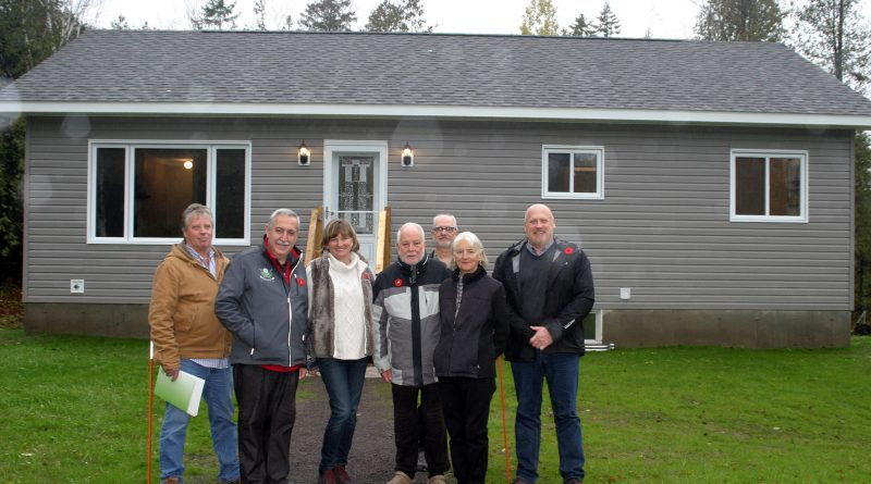 From left, Kerry Bourgaize, Coun. Eli El-Chantiry, Kelley Foley, Don Goodwin, Guildcrest Homes' George Tireney, Linda Couturier and Guildcrest Homes' Sean Kelly pose in front of rural Ottawa's first coach house. Photo by Jake Davies