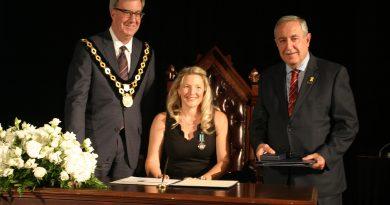 Dunrobin's Emily Glossop signs the Order of Ottawa alongside Mayor Jim Watson and Coun. Eli El-Chantiry at a City Hall ceremony Thursday, Nov. 22. Photo by Jake Davies