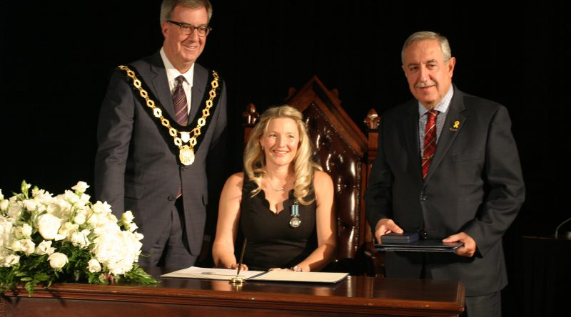 Dunrobin's Emily Glossop signs the Order of Ottawa alongside Mayor Jim Watson and Coun. Eli El-Chantiry at a City Hall ceremony Thursday, Nov. 22. Photo by Jake Davies