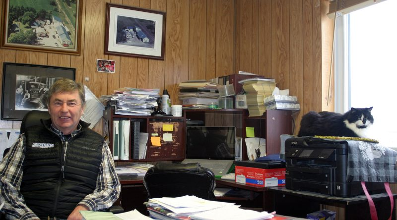 Kinburn Farm Supplies Inc. owner John Herrick sits in his office. Above his right should is the original owner and his team in a photo that dates back to the 1930s. Photo by Jake Davies