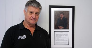 St. George's Warden Tom Jones stands beside a framed photo honouring Amy Newell's devotion to the church. Photo by Jake Davies