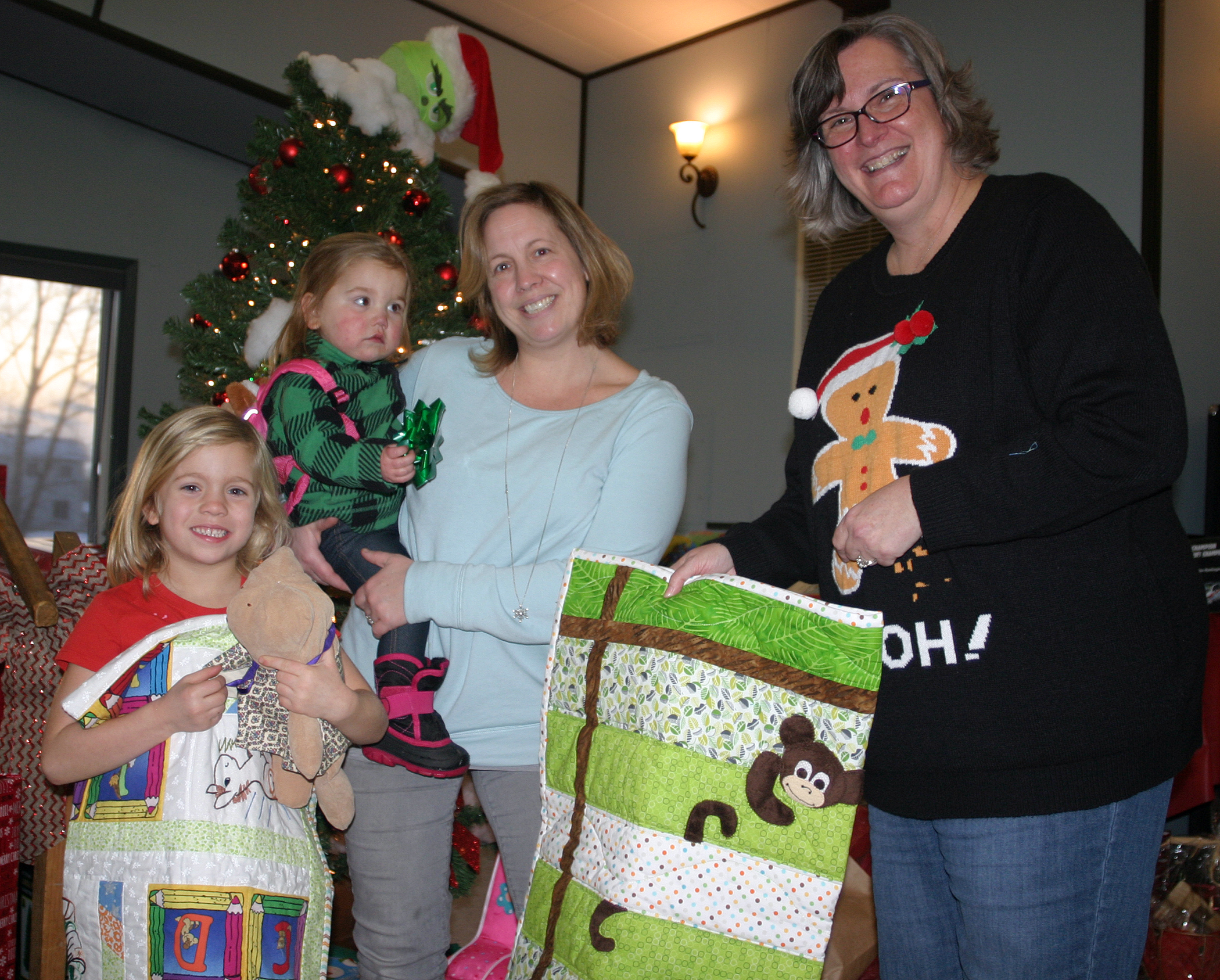 Each child at the party received a handmade quilt as part of their gift bag. From left are Brynn, 5, Jovie, 1, and Rhonda Convery with Kanata Quilt Guild President Brigid Whitnall. Photo by Jake Davies