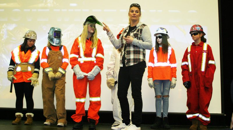 Ironworker Jamie McMillan, with the help of some young volunteers, shows off all the diferent uniforms she wears at her job. Photo by Jake Davies