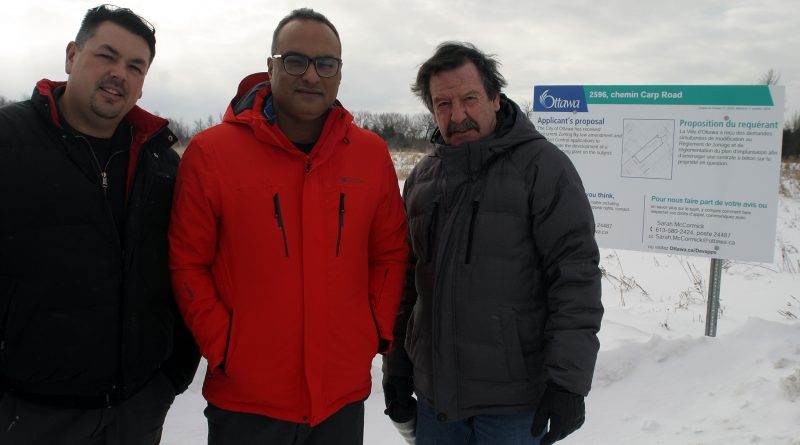 From left, homeowners Mark Demers, Vinod Chaudhary and Emil Morvan pose in front of the city sign at the end of the Newill Place cul-de-sac. Photo by Jake Davies