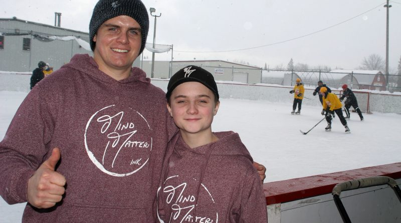 From left, Alex and brother Kaelan Carlson pose for a photo last year while the Hockey4Humanity tournament rages in the background. Photo by Jake Davies