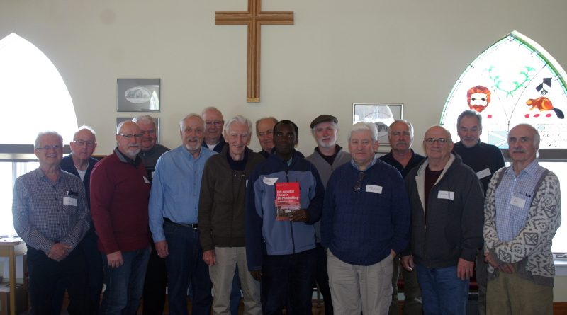 Jean and the Men's Ministry pose for a photo following Jean's presentation. Photo by Jake Davies