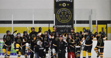 The Warriors pose for a photo with their banner yesterday, after a grueling practice run by uOttawa assistant coach and Carp native Brent Sullivan. Photo by Shelley Welsh