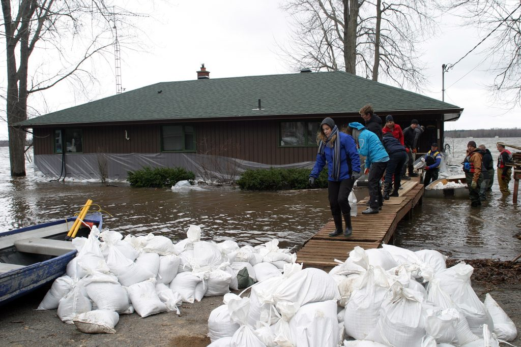 Willola Beach residents form a chain over a small bridge to continue sandbagging a home already surrounded by water. Photo by Jake Davies