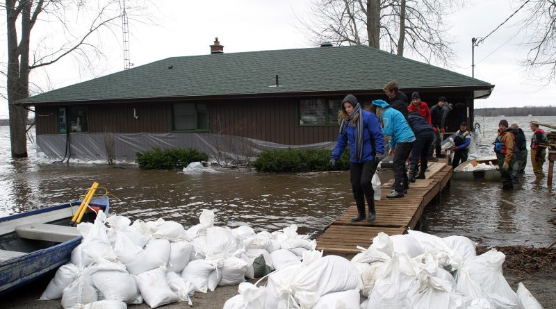 Residents in Willola Beach work on their sandbag wall despite their home being surrounded by water last week. Photo by Jake Davies