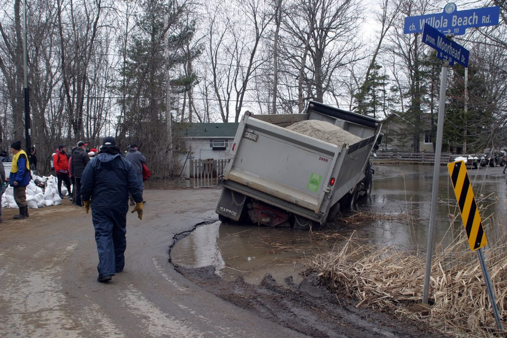 This dump truck was inches away from tipping after trying to sneak by the sandbagging station. Getting it unstuck caused significant delays in flood relief preparations. Photo by Jake Davies