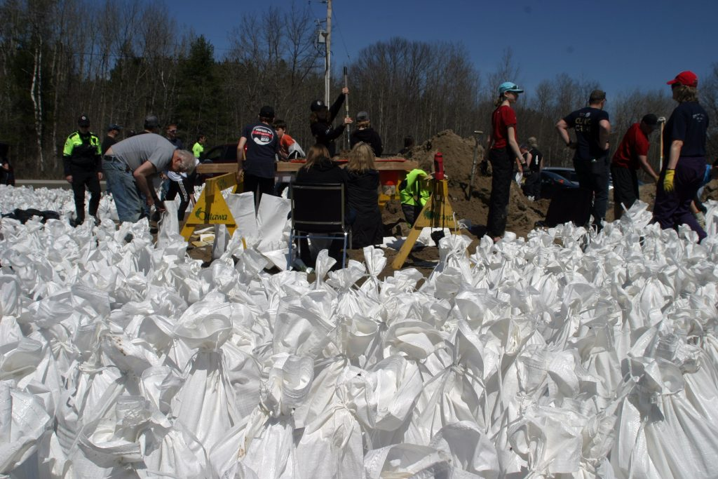 Thanks to a strong showing of volunteers yesterday and today, sandbag fillers were able to build up a surplus that had disappeared Saturday morning. Photo by Jake Davies