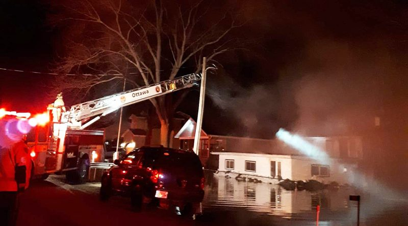 A Bayview Drive home in the flood zone caught fire last night. The residents had evacuated the home earlier. Photo by Norman Hubert