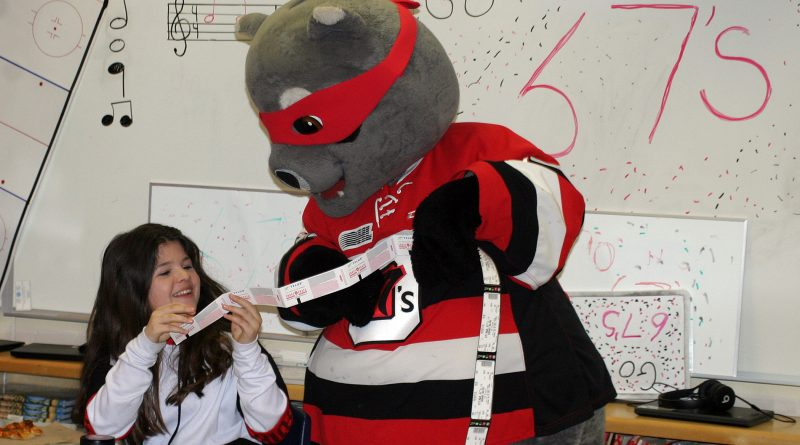 Grade 5/6 student Savannah Swire gets a couple of 67's playoff tickets from Riley the Racoon. Photo by Jake Davies