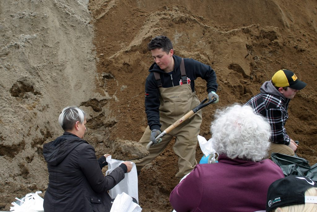 Volunteer firefighter Ash Weaver, whose basement was flooded and heavily damaged in 2017, was filling sandbags at St. Gabriel's Church yesterday. Photo by Jake Davies