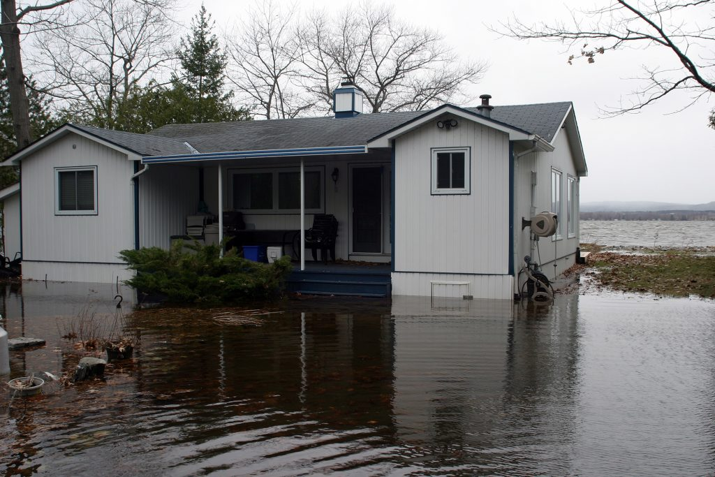 One of the Bayview Drive houses now surrounded by water while three-foot Ottawa River waves crash on the shore behind it. Photo by Jake Davies