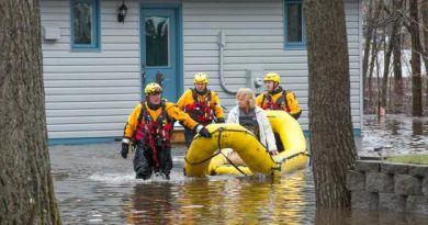 Lt. Paul Champion-Demers and his fellow Water Rescue technicians bring a resident to safety. Courtesy Wayne Cuddington / Postmedia