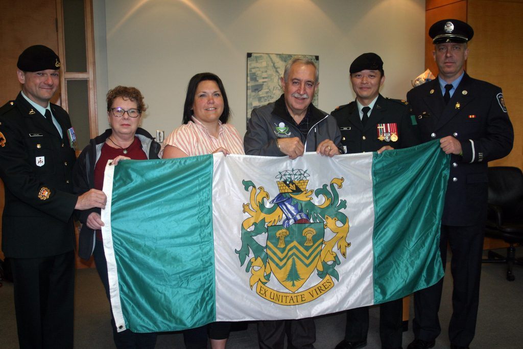 From left, Master Warrant Officer Chris LeBlanc, WCDR's Angela Bernhardt, WCDR's Shannon Todd, Coun. Eli El-Chantiry, Major Kevin Wong and firefighter Paul Asmis pose with West Carleton's township flag. Photo by Jake Davies