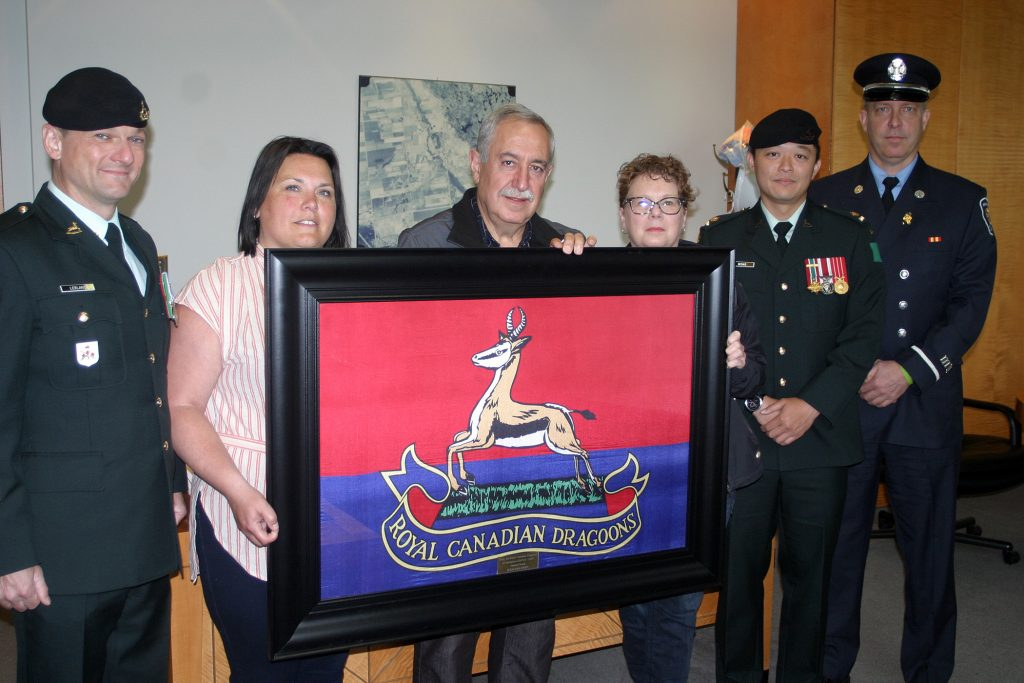 The same crew poses with the Royal Dragoon regimental flag. Photo by Jake Davies