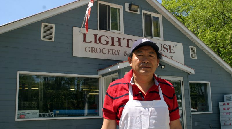 Lighthouse Restaurant owner Ji, popped out of the kitchen on re-opening day to pose for this photo. Photo by Jake Davies