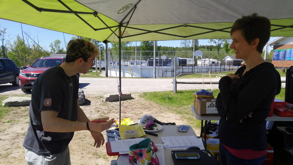 WCSS student Alex Desjardin tells his story of needed volunteer hours to WCDR co-chair Alex Lesnick while registering to help with clean-up. Photo by Jake Davies