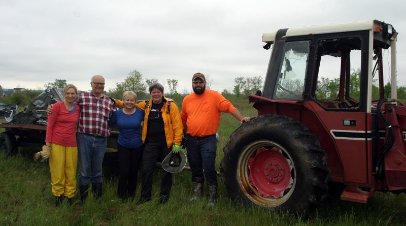 From left, Christiane Stieber, Michael Stieber, Jill Seymour, Ruth Sirman and Tim Hayes pose for a photo during a break in tornado clean-up work last Sunday. Notice Michael's tractor no longer has windows due to tornado damage. Photo by Jake Davies
