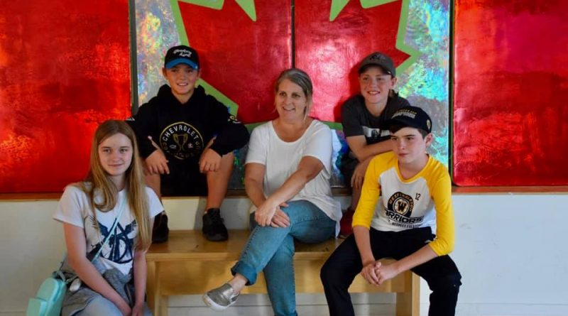 Artist Sarah Moffatt, posing with some West Carleton Warriors Good Deeds champs, made this beautiful Canada Flag especially for Light Up Dunrobin. Photo by Shelley Welsh