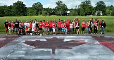 The Borgs' annual Canada Day party people pose behind the massive Canada Day flag they painted on the Carp Road June 30. Courtesy Ken Borg