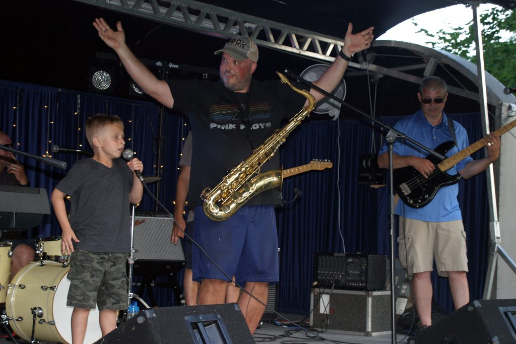 J.J. Craig, 6, performs I'm Still Standing at last week's Concerts in the Park while Dave Rama pumps up the crowd. Photo by Jake Davies