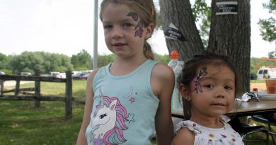 From left, Harbour girls June, 6, and Samantha, 2, show off their amazing art work after gettting painted at the Kids Fair Saturday afternoon. Photo by Jake Davies