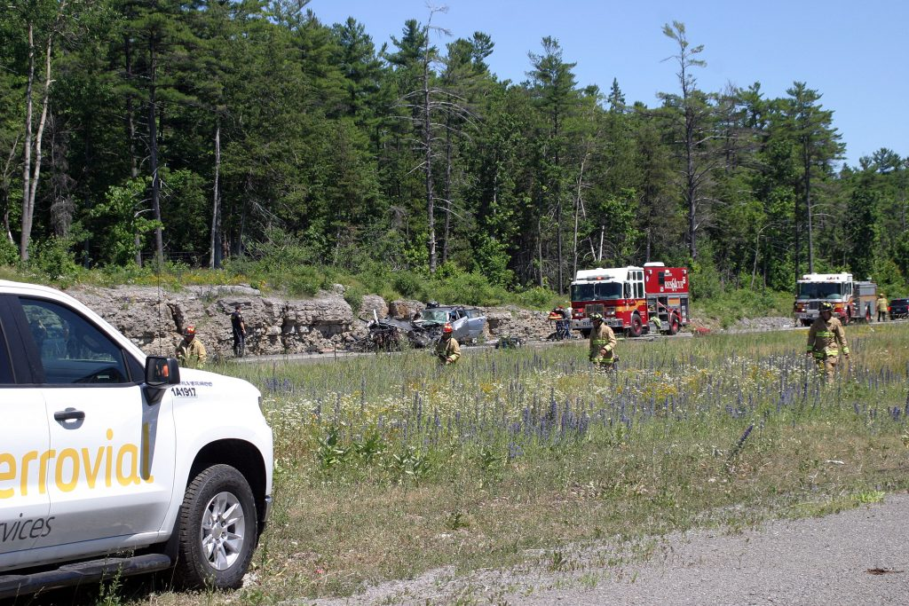 Ottawa firefighters comb the grass median looking for debris from the multi-vehicle collision. Photo by Jake Davies