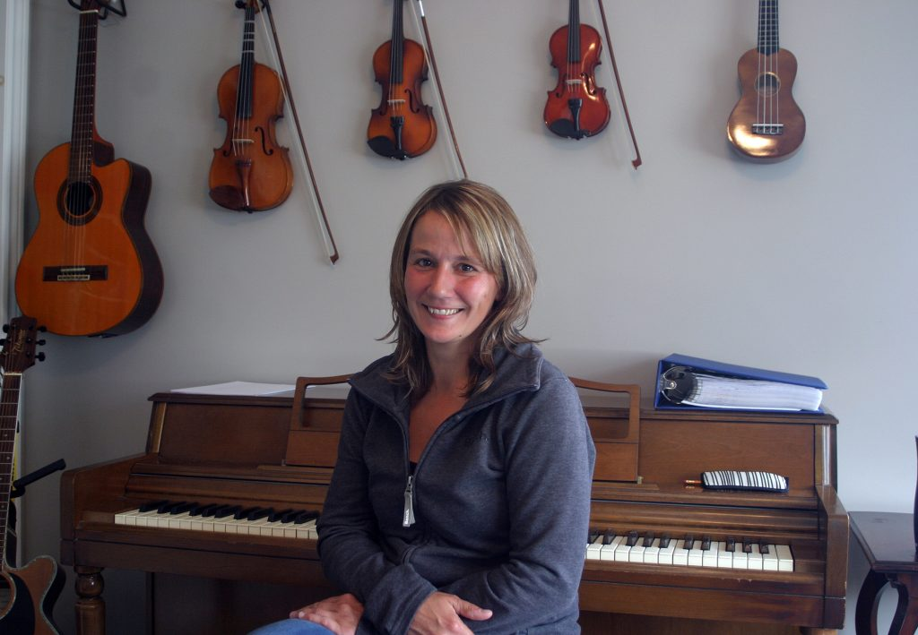 Musician Jennifer Johnson poses at her piano in her new studio at the Village Station in Carp. Photo by Jake Davies