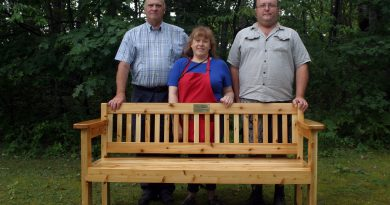 From left, Ches Booth, market manager Cindy Pratt and memorial builder and marker vendor Chris Kritsch pose with the memorial bench in honour of Judy Booth. Photo by Jake Davies