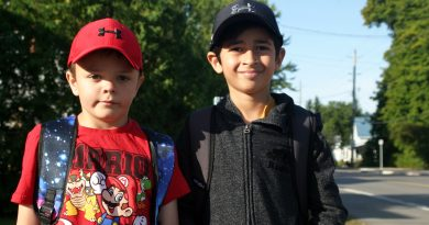 Kinburn's Pearce, 7, and Arjun, 7, are excited to reunite with their school chums as they wait for the bus on the first day of school today. Photo by Jake Davies