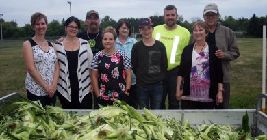 Kinburn Community Association members and volunteers pose in front of 35 dozen corn husks at last Friday's annual Kinburn Corn Roast. Photo by Jake Davies