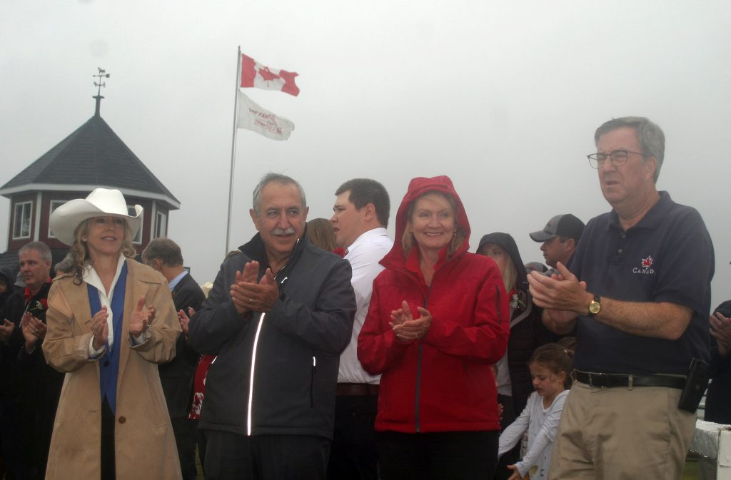 From left, MPP Dr. Merrilee Fullerton, Coun. Eli El-Chantiry, MP Karen McCrimmon and Mayor Jim Watson applaud during speeches at the 156th Carp Fair Ceremonial Parade with the Carp Fair flag blowing in the breeze in the background. Photo by Jake Davies