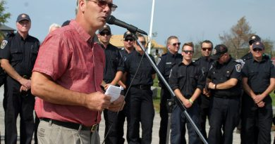 Dunrobin Community Association President and West Carleton Disaster Relief co-chair Greg Patacairk addresses the community in front of volunteer firefighters who were first on scene at Saturday's one year anniversary of the 2018 tornado. Photo by Jake Davies