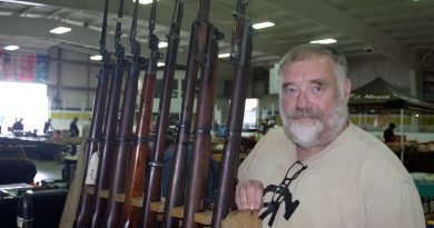 Valley gun show vendor Bill Neslon poses with his collection of World War I and World War II weaponry. Photo by Jake Davies