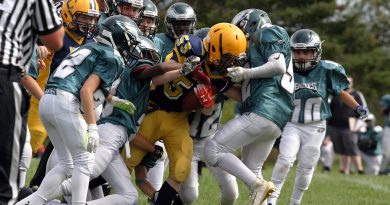 It took the entire Eagles team to tackled Wolverine RB Owen Redmond during last Sunday's pee wee game. And they still got a face-masking penalty on the play. Photo by Jake Davies
