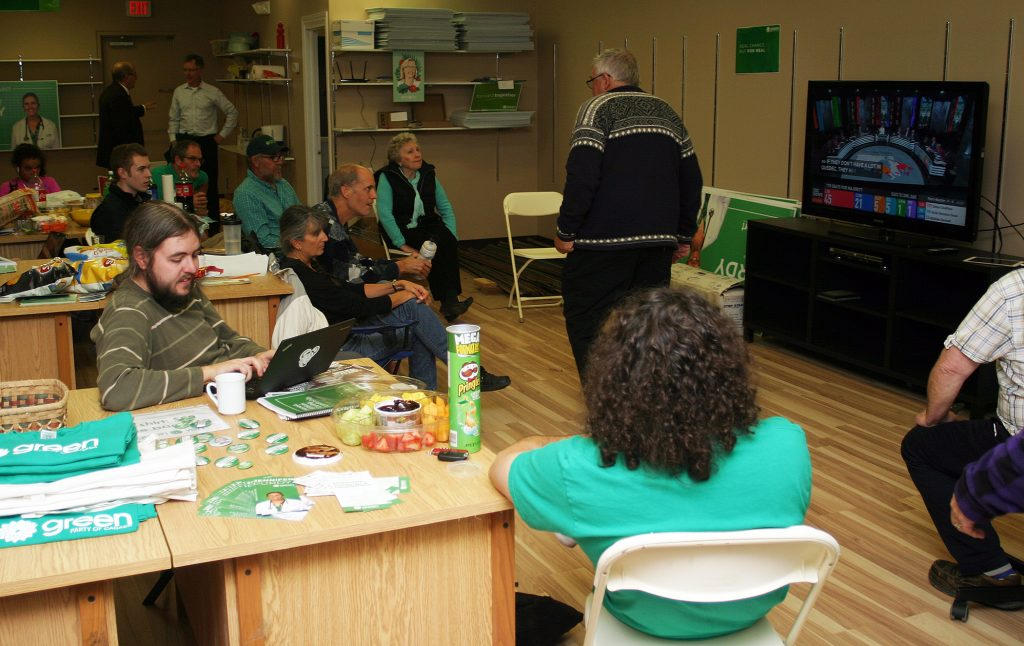 Kanata-Carleton Green Party supporters watch coverage of the election from their heaquarters. Photo by Jake Davies