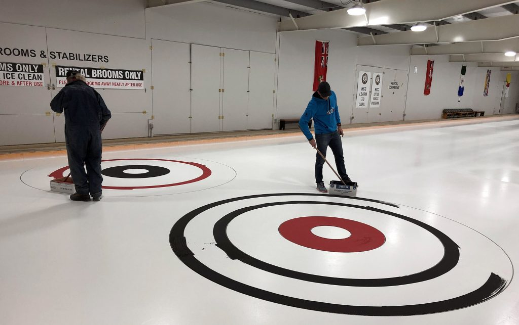 Painting four perfectlly paralell, perfectly round circles, on ice, isn't as easy as it sounds. Courtesy the HCC