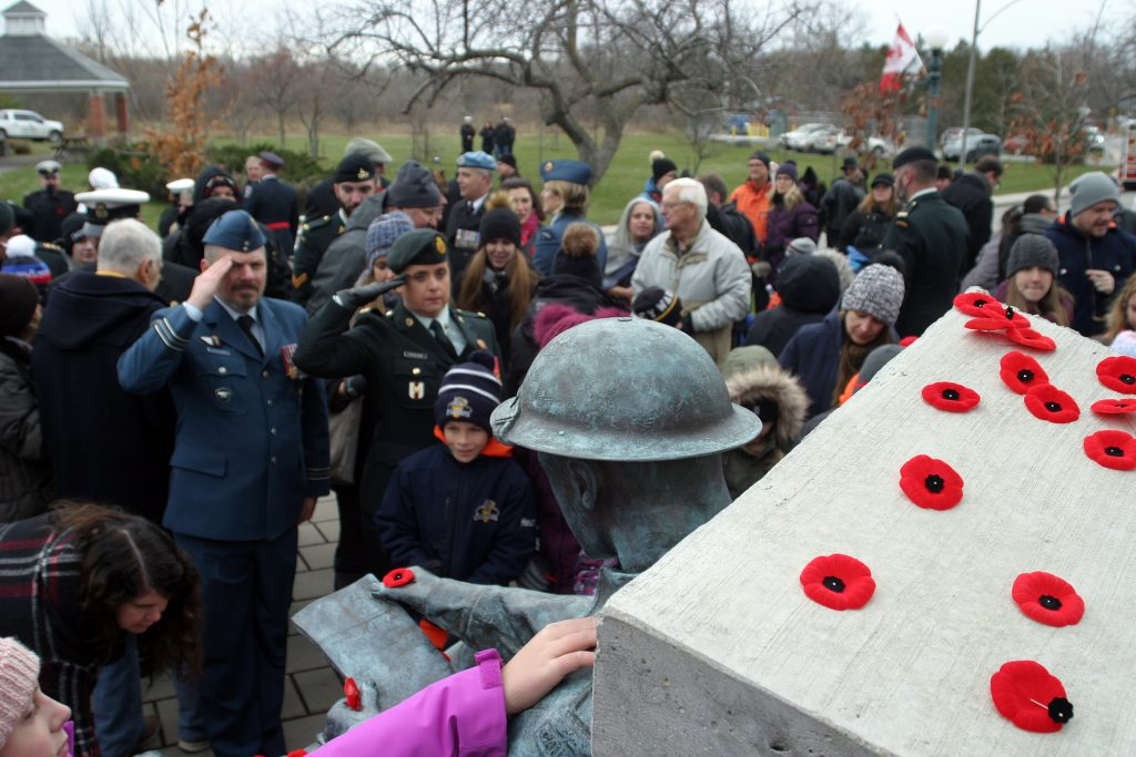 Those in attendance place their poppies on the memorial following the service. Photo by Jake Davies