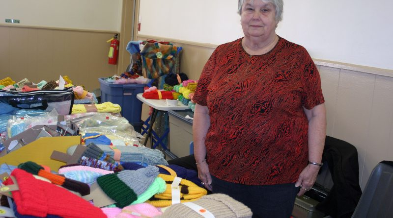 Kinburn craft sale vendor Pat Vallaincourt, with husband René strategically hidden in the background, has never missed a fair in 39 years. Photo by Jake Davies