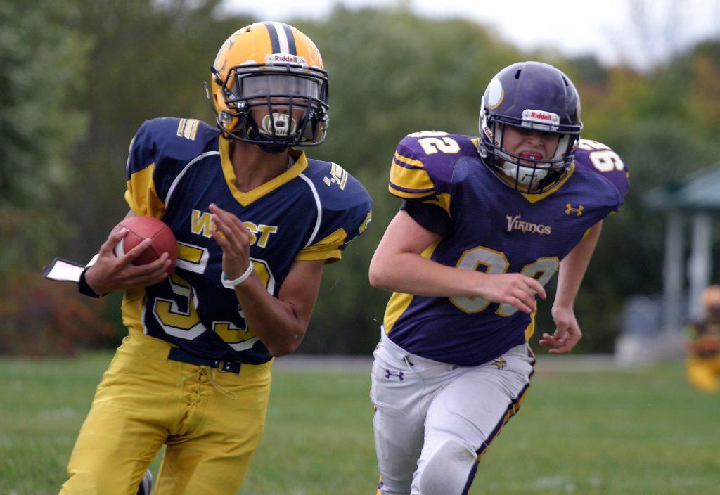 Wolverine quarterback Keegan Brunet runs away from a Gatineau Viking during an early season win. Photo by Jake Davies